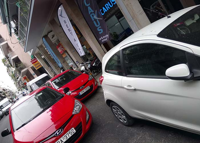 red and white car rentals in Athens