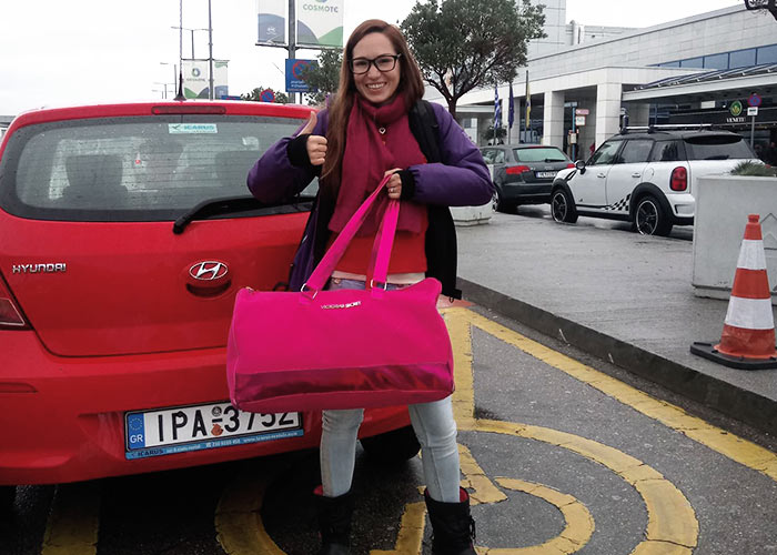 Girl with pink bag next to red hyundai car rental